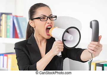 Woman with megaphone. Angry young businesswoman shouting at megaphone while talking on the phone