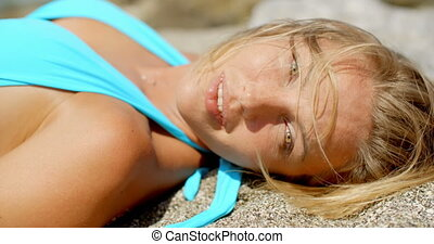 Woman with Messy Hair Suntanning on Sandy Beach - Smiling...
