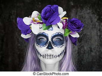 Closeup face of woman with Mexican sugar skull makeup and flowery wreath looking into the camera. Creative, artistic, Halloween concept