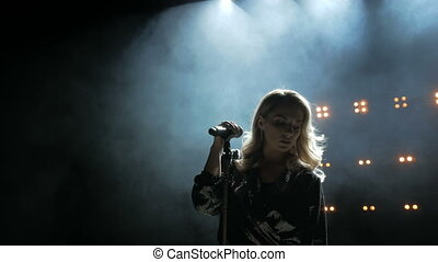 Woman with microphone. Beauty professional singer girl close...