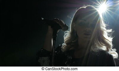 Woman with microphone. Beauty professional singer girl close-up on the stage.