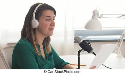 woman with microphone recording podcast at studio -...
