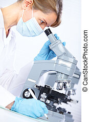 Woman with microscope - Woman working with a microscope in a...
