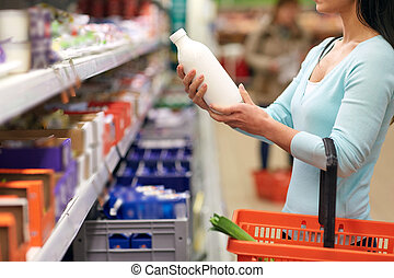 woman with milk bottle at grocery or supermarket