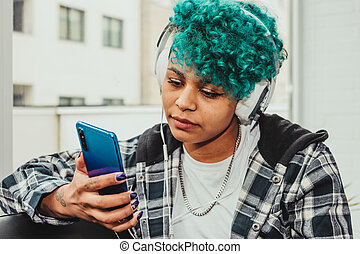 woman with mobile phone and headphones at home sitting on the sofa next to the window