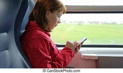 Woman with mobile phone in train