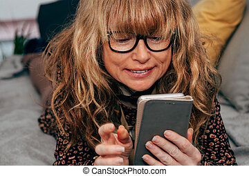 woman with mobile phone on the sofa at home