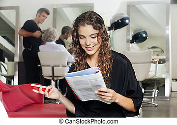 Woman With Mobile Phone Reading Magazine At Hair Salon