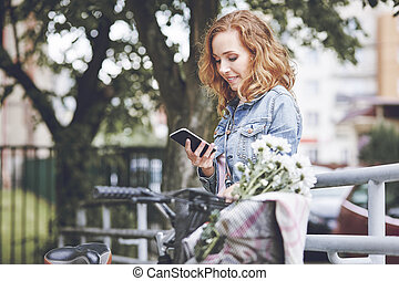 Woman with mobile phone relaxing after the cycling
