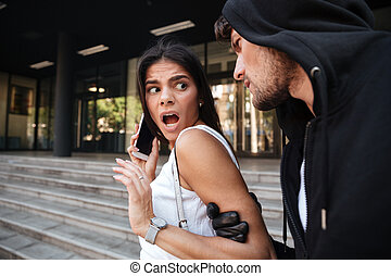 Woman with mobile phone shouting and attacked by criminal...