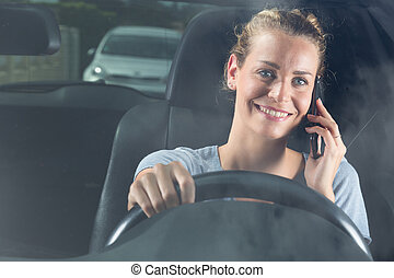 woman with mobile phone smiles in car