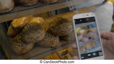 Woman with mobile taking shot of bread in the bakery