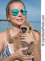 Woman with monkey on the beach - Portrait of smiling woman...