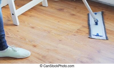 woman with mop cleaning floor at home - people, housework...