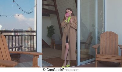 Woman with morning coffee on balcony admiring view