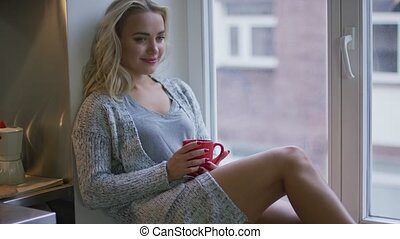 Woman with mug looking out window