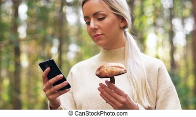 woman with mushroom and smartphone in forest - season and...