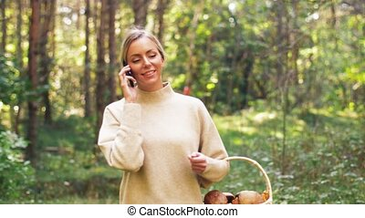woman with mushrooms calling on cellphone in woods - season...