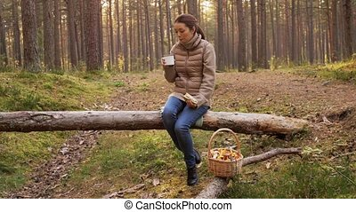 woman with mushrooms drinks tea and eats in forest - picking...
