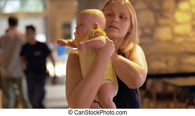 Woman with naughty baby in cafe - Young mother with baby in...