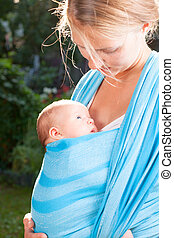 Woman with newborn baby in sling - Mother carrying her child...