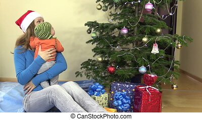 woman with newborn baby look at decorated Christmas fir tree