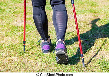 Woman with nordic walking poles on grass