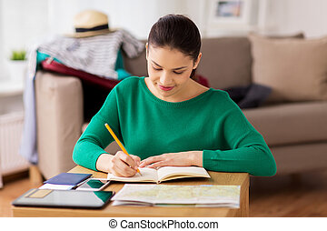 woman with notebook and travel map at home