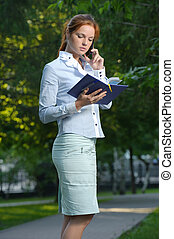 Woman with notebook talking on the phone
