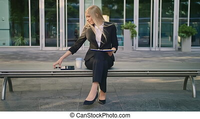 Woman with notepad speaking on phone outdoors. Modern business woman in suit sitting on bench with notepad in hands and having phone call looking away.