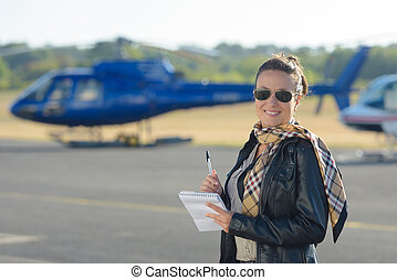 woman with notes in front of a helicopter