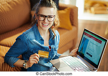 woman with online travel site on laptop holding gold credit card