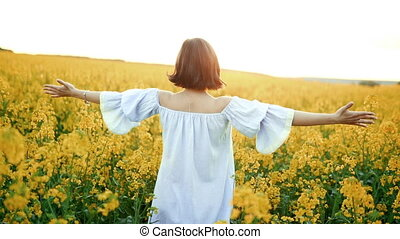 Woman with open arms at sunset in rapeseed yellow flowers...