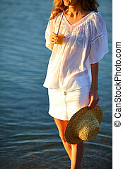 Woman with orange juice and a straw hat in hand on the beach