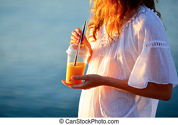 Woman with orange juice in a disposable cup against the sea