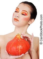 Woman with orange make up holding pumpkin