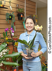 woman with orchid in flower store