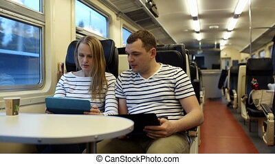 Woman with pad and man with laptop talking in the train