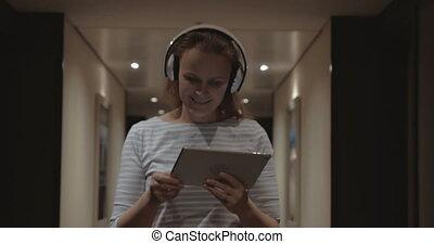 Woman with pad enjoying music in headphones