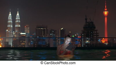 Woman with pad in rooftop pool of night Kuala Lumpur