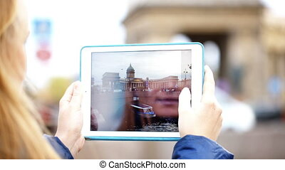 Woman with pad making photos of Kazan Cathedral in St. Petersburg