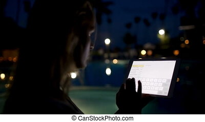Woman with pad on tropical resort in the evening
