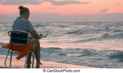 Woman with pad sitting on chair by rough sea