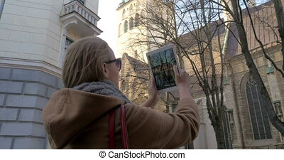 Woman with pad taking photo of historical building