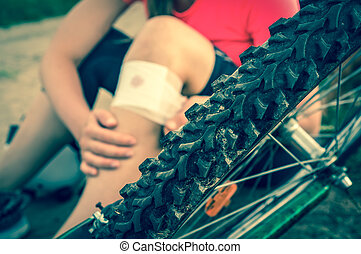 Woman with pain in knee after falling down from bicycle -...