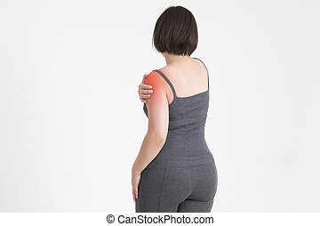 Woman with pain in shoulder on gray background