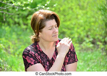 Woman with pain in shoulder on the nature