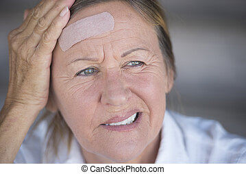 Woman with painful headache and band aid
