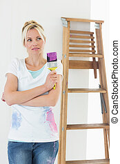 Woman with paint brush looking away in new house