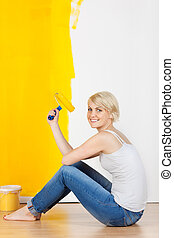 Woman With Paint Roller Sitting On Floor
